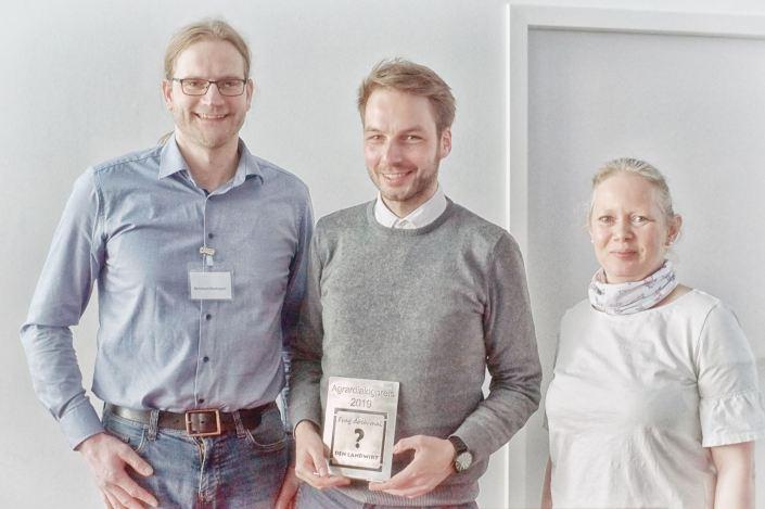 Dirk Fisser nimmt den Agrardialogpreis von Bernhard Barkmann und Nadine Henke entgegen